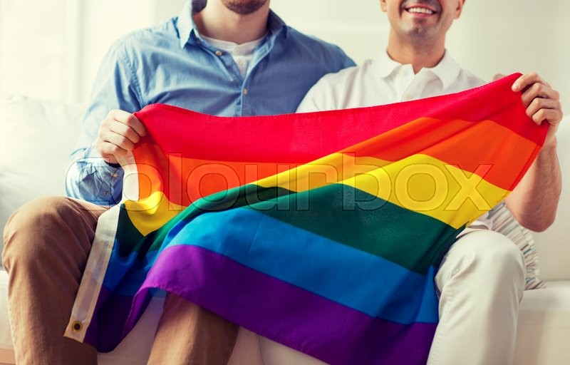 Stock image of 'people, homosexuality, same-sex marriage, gay and love concept - close up of happy male gay couple hugging and holding rainbow flag at home'