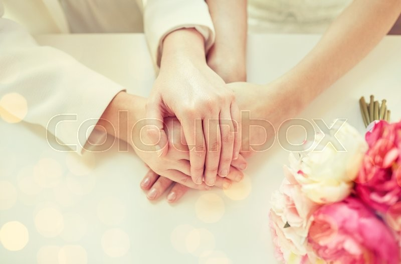 Stock image of 'people, homosexuality, same-sex marriage and love concept - close up of happy married lesbian couple hands over holiday lights background'