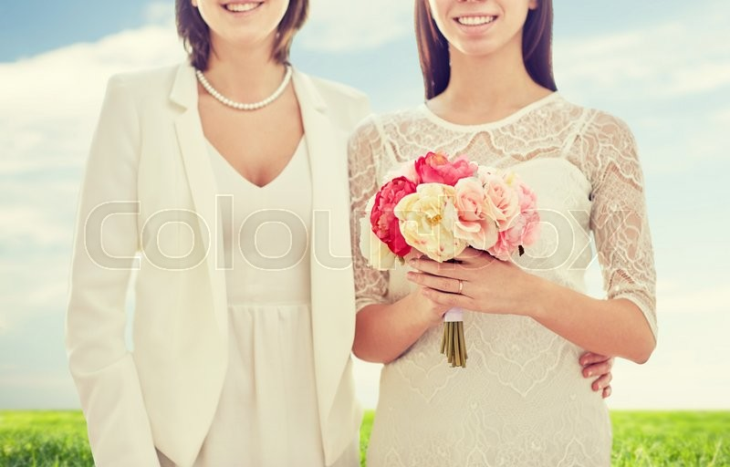 Stock image of 'people, homosexuality, same-sex marriage, honeymoon and love concept - close up of happy married lesbian couple with flower bunch over blue sky and grass background'