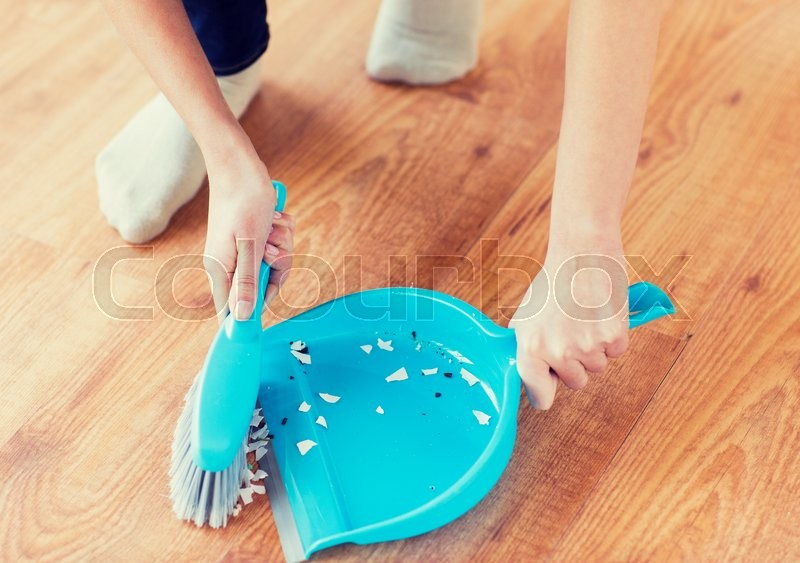 Stock image of 'people, housework, cleaning and housekeeping concept - close up of woman with brush and dustpan sweeping floor at home'