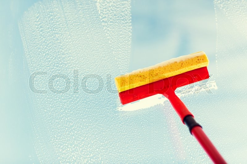 Stock image of 'people, housework and housekeeping concept -close up of hand cleaning window glass with sponge mop and foam'