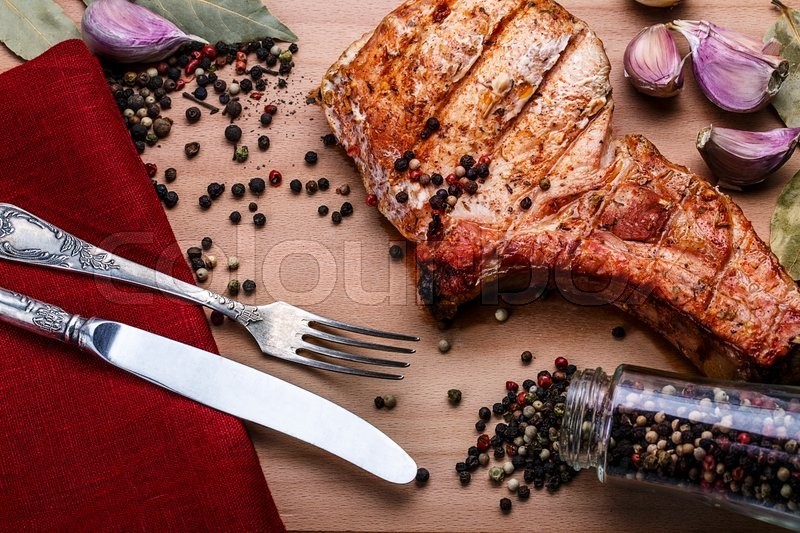 Stock image of 'Beef steaks with spices on a wooden tray. Barbecue food'