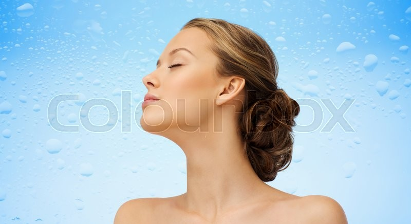 Stock image of 'beauty, people and health concept - young woman face with closed eyes and shoulders side view over water drops on blue background'