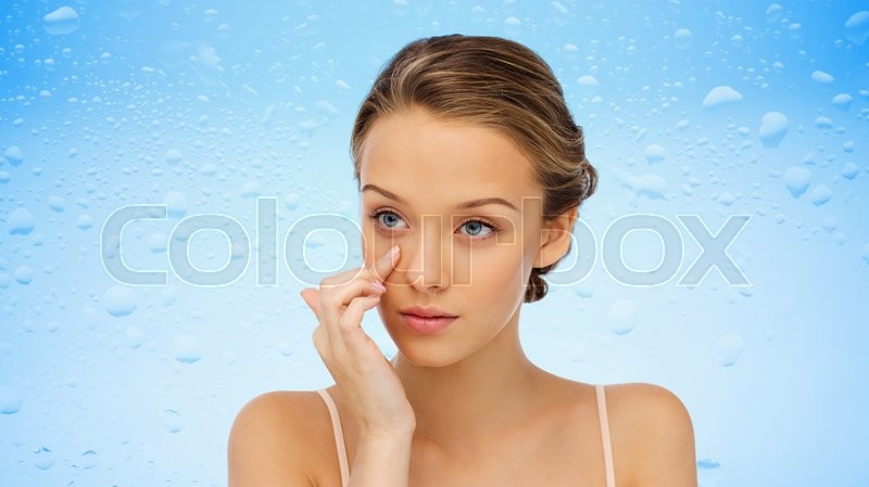 Stock image of 'beauty, people, cosmetics, skincare and health concept - young woman applying cream to her face over water drops on blue background'