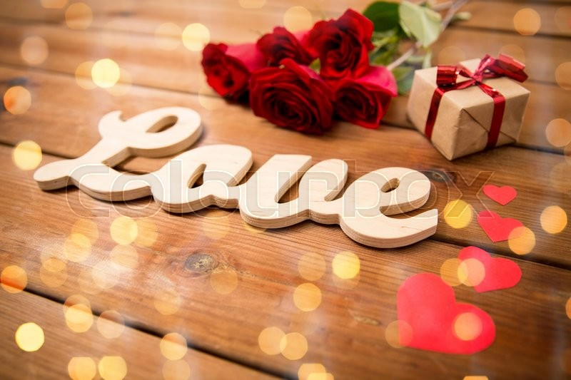 Stock image of 'love, romance, valentines day and holidays concept - close up of gift box, red roses and hearts on wood over lights background'