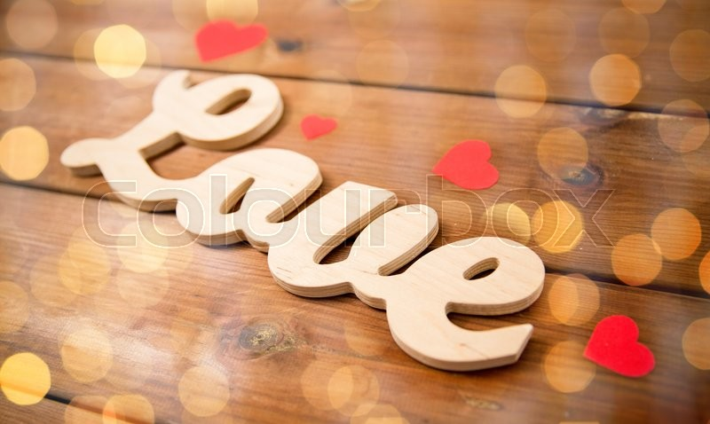 Stock image of 'love, date, romance, valentines day and holidays concept - close up of word love with red paper hearts on wood'