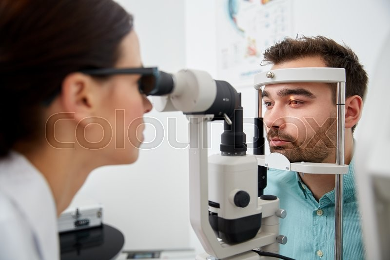 Stock image of 'health care, medicine, people, eyesight and technology concept - optometrist with non contact tonometer checking patient intraocular pressure at eye clinic or optics store'