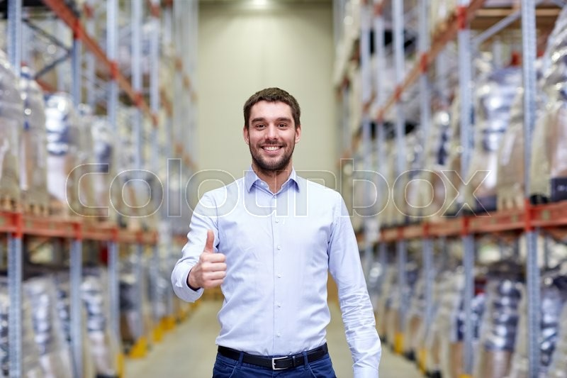 Stock image of 'wholesale, logistic, business, export and people concept - happy man at warehouse showing thumbs up gesture'