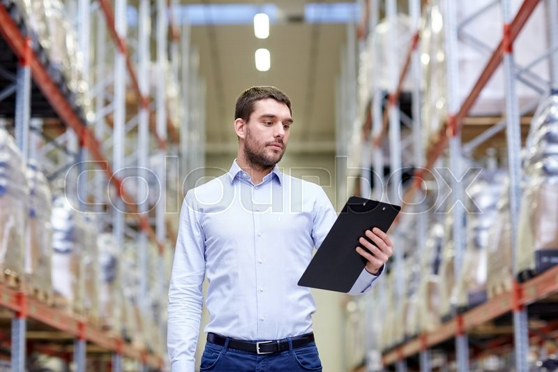 Stock image of 'wholesale, logistic, business, export and people concept - man or manager with clipboard checking goods at warehouse'