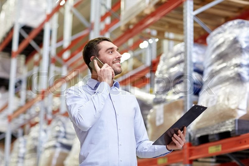Stock image of 'wholesale, logistic, business, export and people concept - smiling businessman with clipboard calling on smartphone at warehouse'