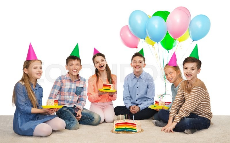 Stock image of 'childhood, holidays, celebration, friendship and people concept - happy smiling children in party hats with birthday cake and balloons'