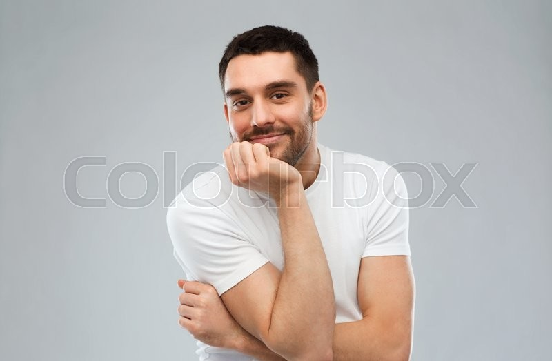 Stock image of 'expression and people concept - happy smiling man over gray background'