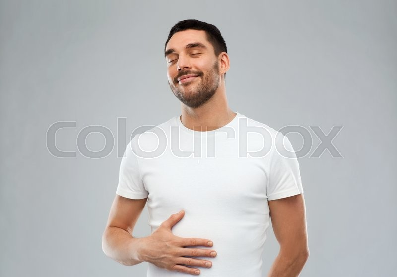 Stock image of 'satisfaction and people concept - happy full man touching his tummy over gray background'