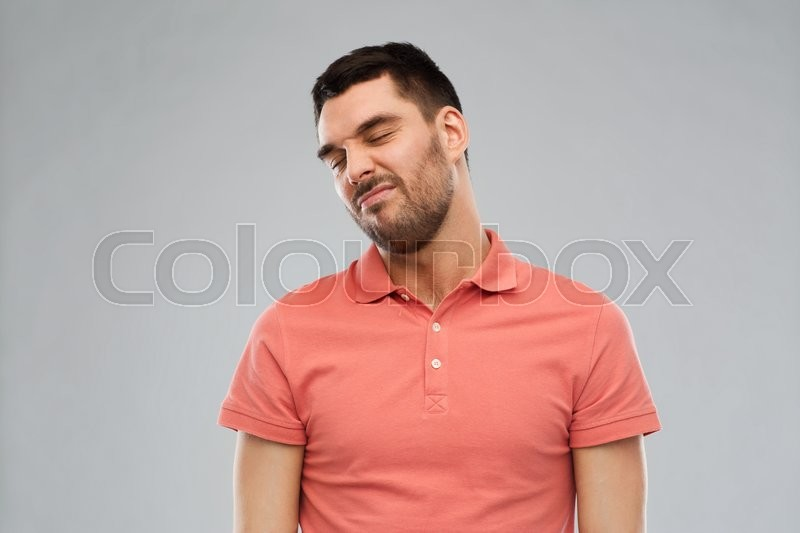 Stock image of 'emotion and people concept - young wrying man over gray background'