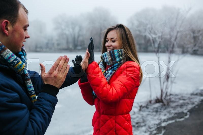 Stock image of 'beautiful young couple staning and clapping in the park'