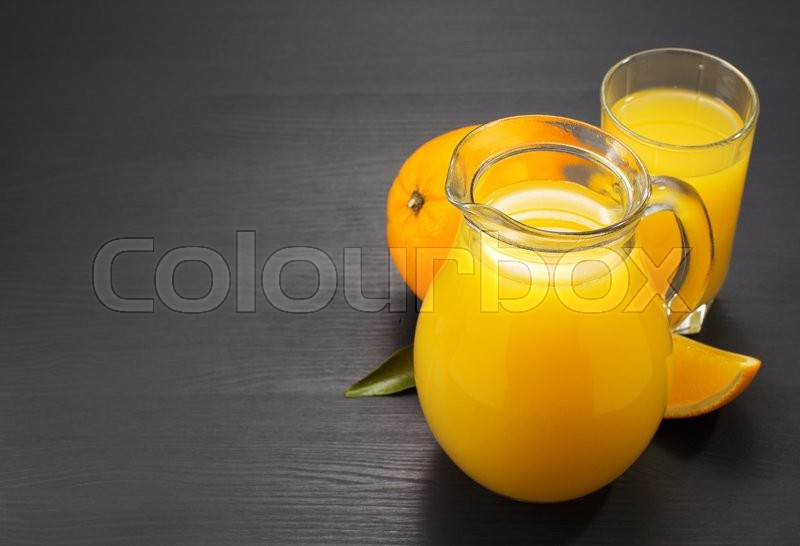 Stock image of 'glass pitcher and orange juice on wooden background'