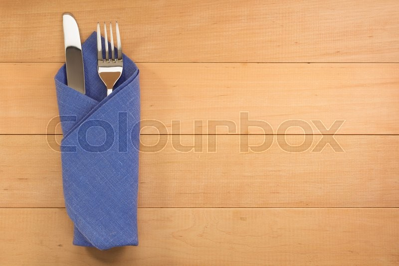 Stock image of 'knife and fork at napkin on wooden background'