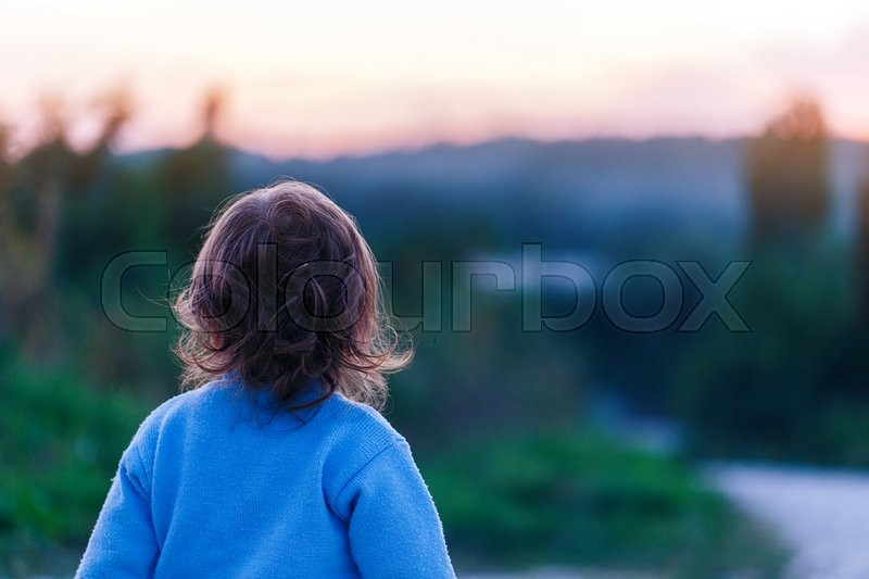 Stock image of 'girl child looking back at sunset landscape '
