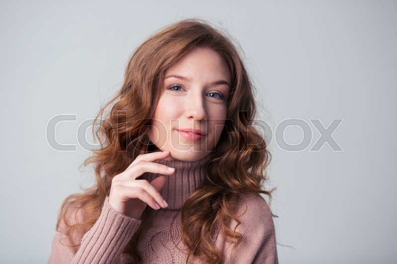 Stock image of 'Happy young woman looking at camera over gray background'