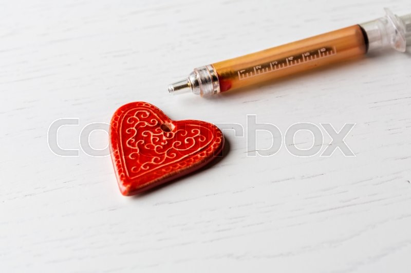 Stock image of 'Ceramic heart ready to be rescued with a syringe pen. White wooden background'