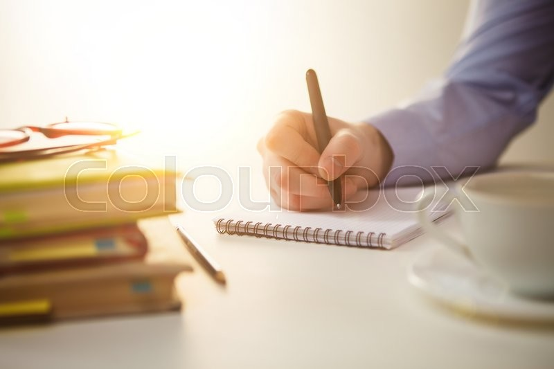 Stock image of 'The male hand with a pen and the cup of coffee and notebook'