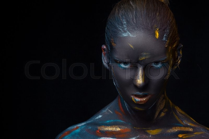 Stock image of 'Portrait of a young woman who is posing covered with black paint in the studio on a black background'