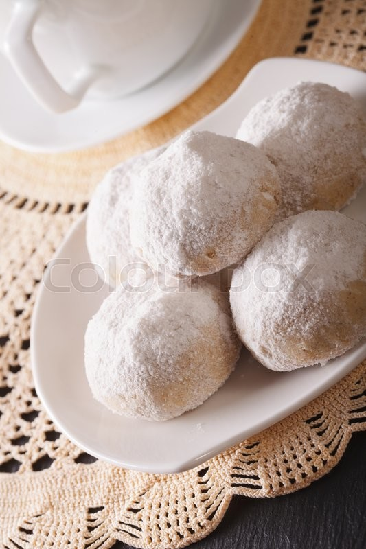 Stock image of 'Spanish nut cookies with powdered sugar close-up on a plate. vertical\'