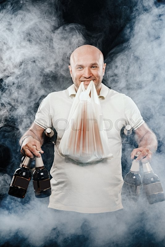 Stock image of 'happy man with lots of beer on a black background'