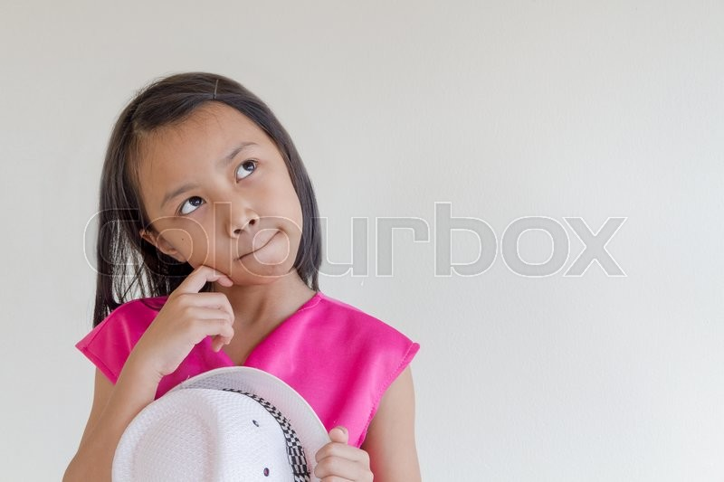 Stock image of 'Adorable asian kids in a pink dress with white hat looking for something'