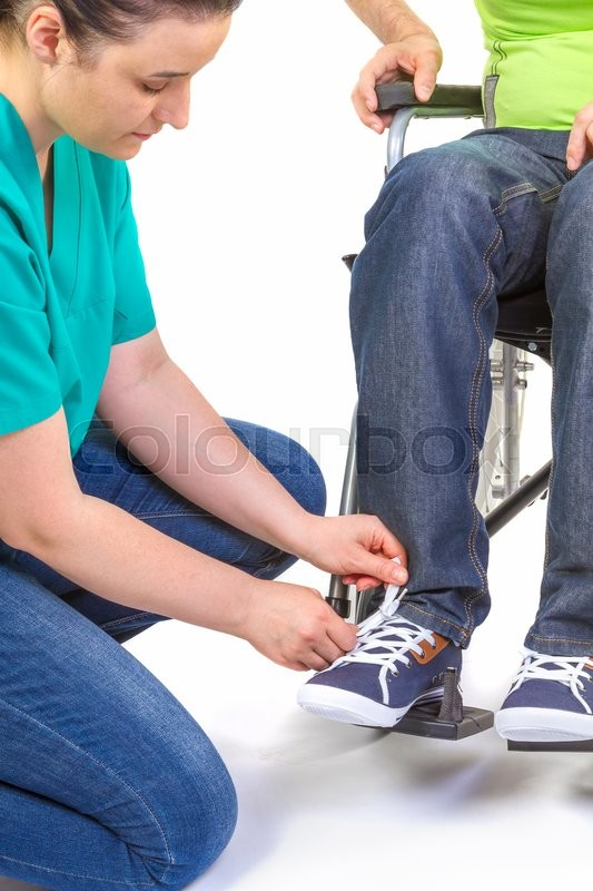 Stock image of 'Nurse helping a disabled young man in wheelchair get dressed.'