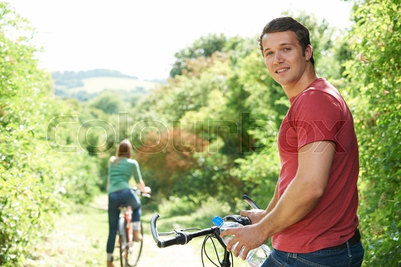 Stock image of 'Yoing Couple Cycling In Countryside'