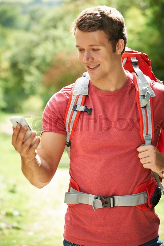 Stock image of 'Man Using Smartphone To Plan Route On Hike'