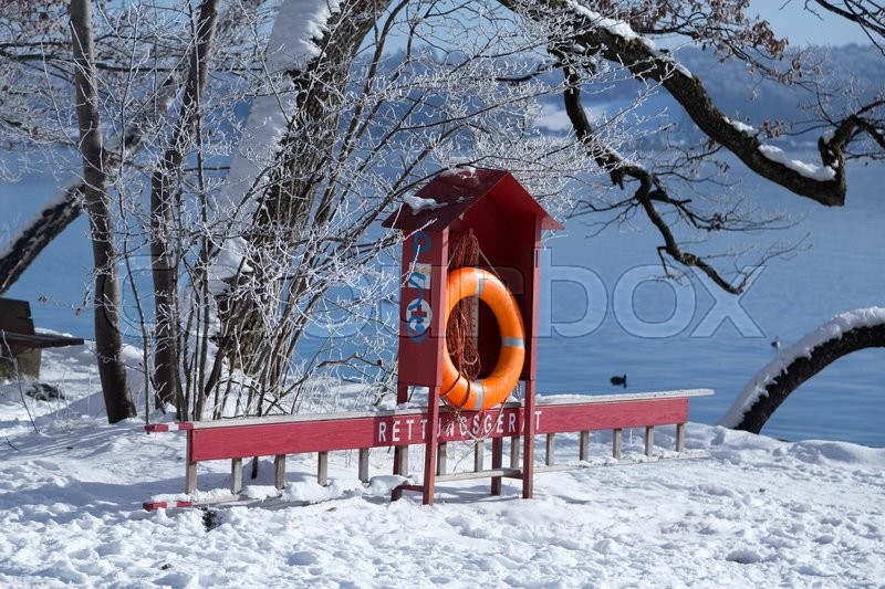 Stock image of 'A lifebuoy close to the lake and snow on the ground'