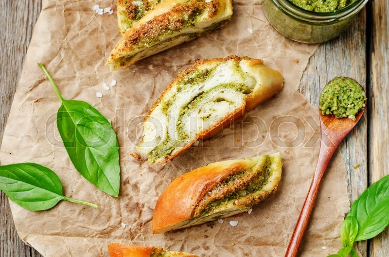 Stock image of 'braided basil pesto bread on a dark wood background. toning. selective Focus'