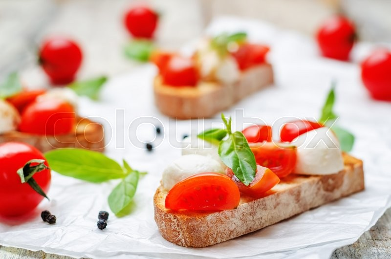 Stock image of 'Caprese bruschetta on a white wod background. toning. selective Focus'