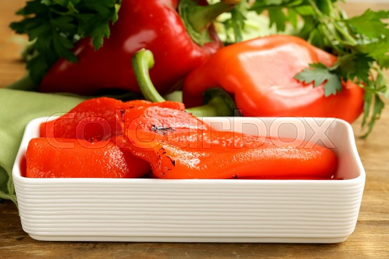 Stock image of 'grilled red bell pepper in a white bowl on wooden table'