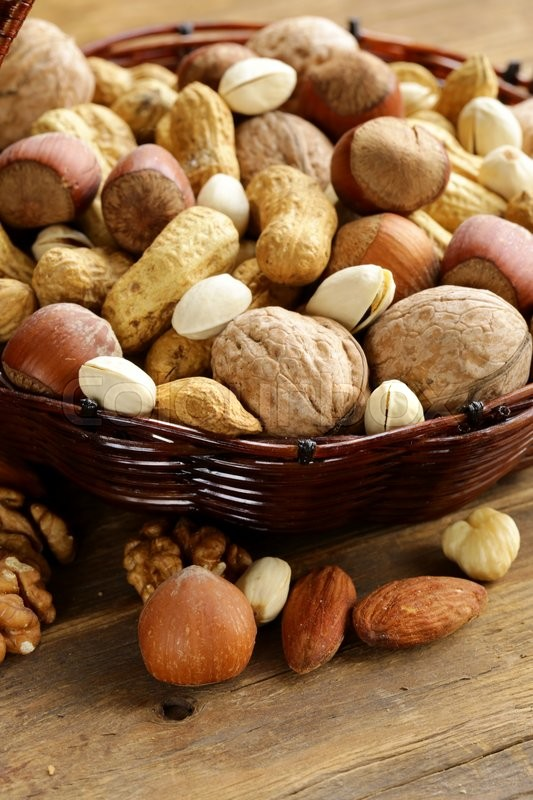 Stock image of 'Assortment of different nuts (peanuts, hazelnuts, pistachios, walnuts)'