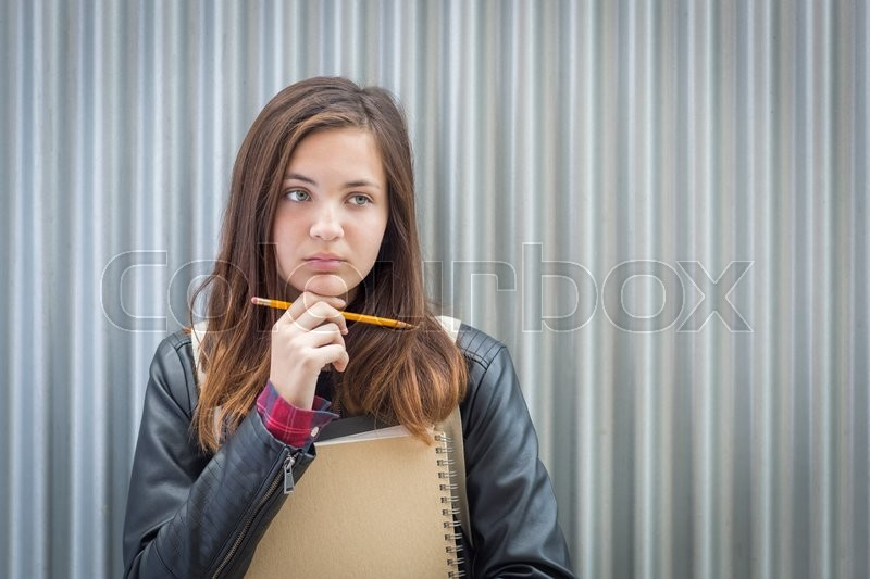 Stock image of 'Pretty Young Melancholy Female Student With Books and Pencil Looking to the Side.'