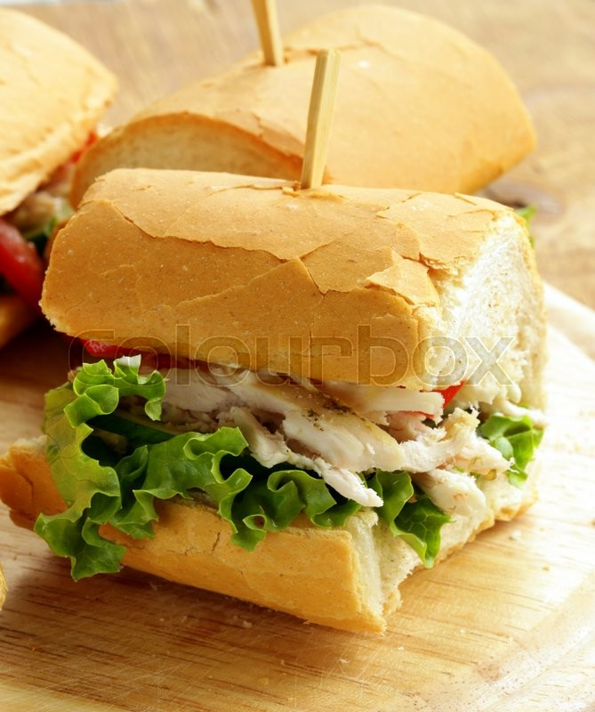 Stock image of 'panini sandwich with chicken and vegetables on a wooden board'
