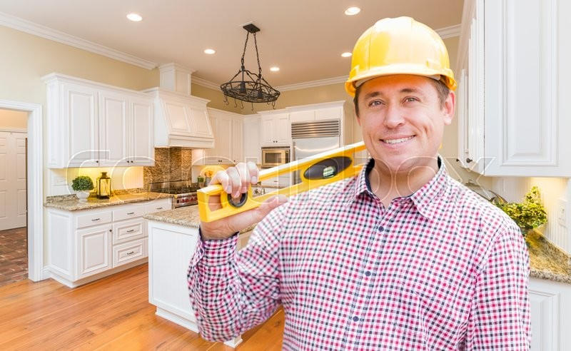Stock image of 'Smiling Contractor with Level Wearing Hard Hat Standing In Custom Kitchen.'