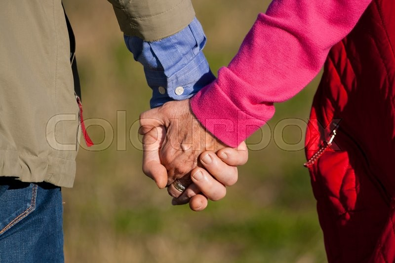 Stock image of 'A man and a woman, both in their late 60s, holding hands. Closeup of their hands on a blurred background.'