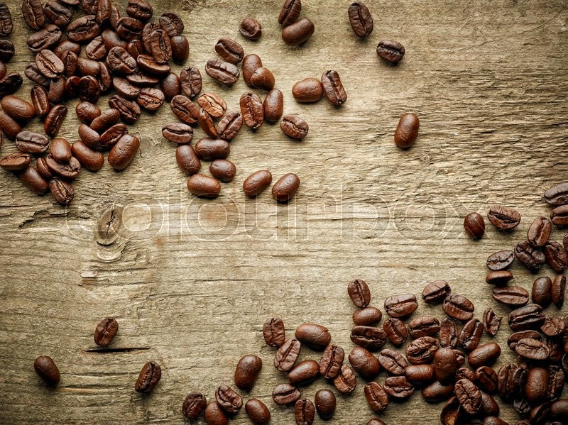 Stock image of 'Coffee beans on wooden table, top view'