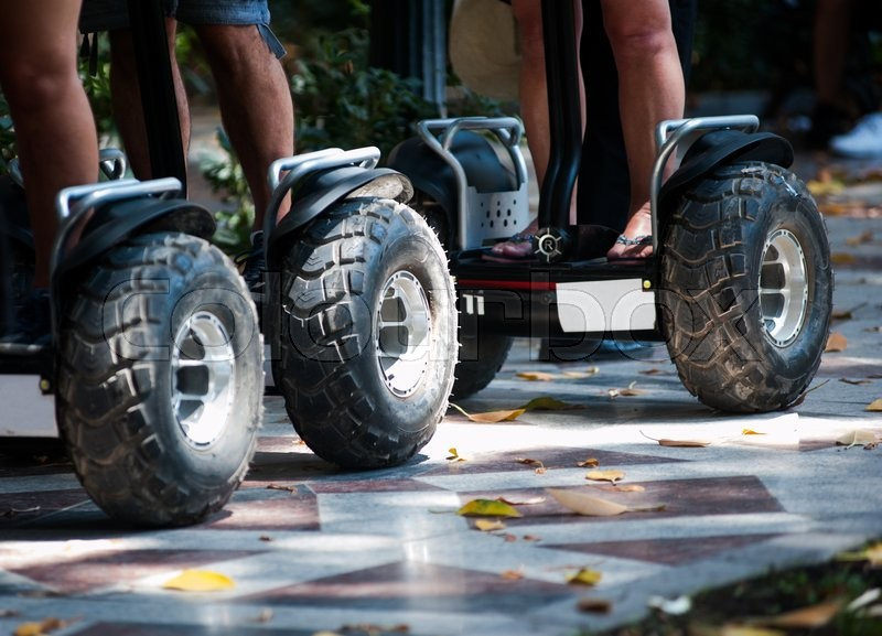 Stock image of 'Wheels of electric scooters in the park close up'
