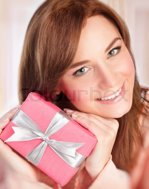 Stock image of 'Closeup portrait of happy smiling woman holding in hands present wrapped in pink paper with silver ribbon, receive gift in Valentine day'