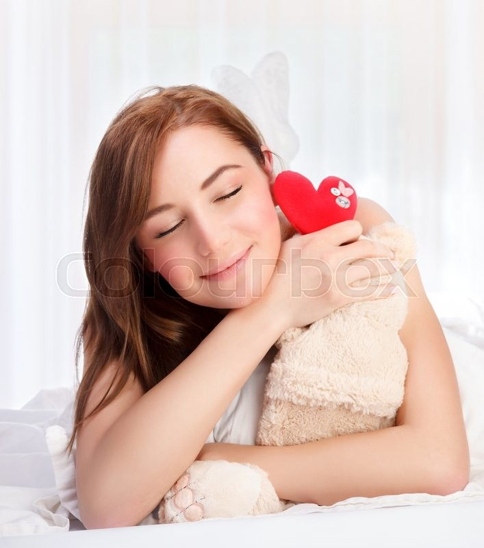 Stock image of 'Closeup portrait of cute young girl lying down in her bed at home, closing eyes of pleasure, receive soft bear toy with red heart as gift for Valentine day'