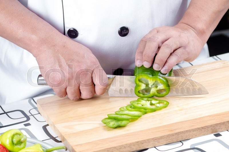 Stock image of 'Chef cutting green bell pepper and vetgetable on cutting board'
