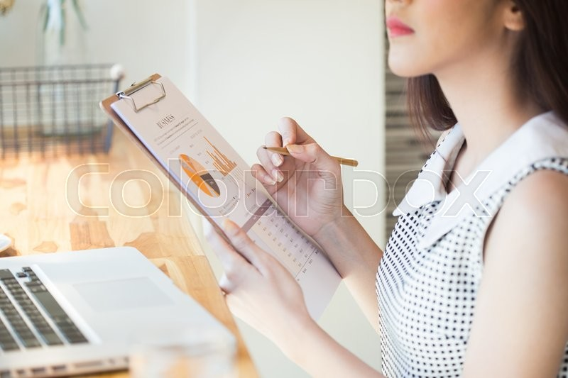 Beautiful business woman using a laptop computer and writing on business document. Selective focus on document, stock photo