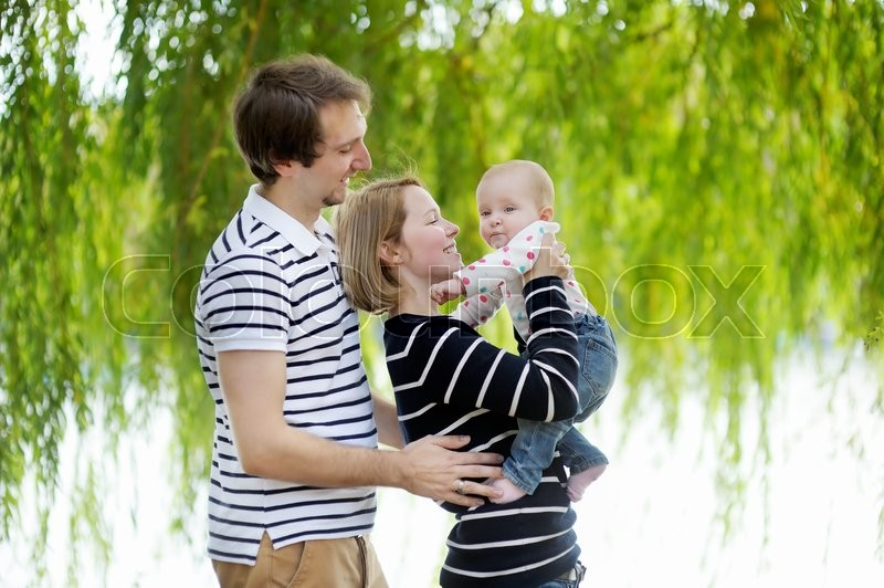 Stock image of 'Happy parenthood: young parents with their sweet baby girl in sunny park'