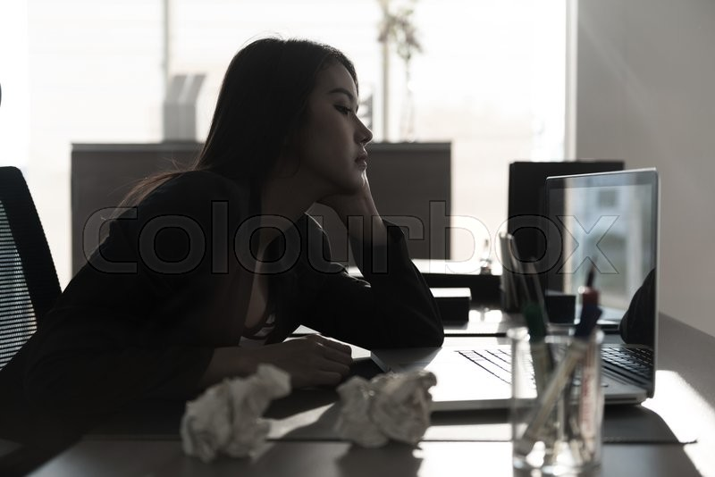 Stock image of 'Unhappy businesswoman sitting at desk'