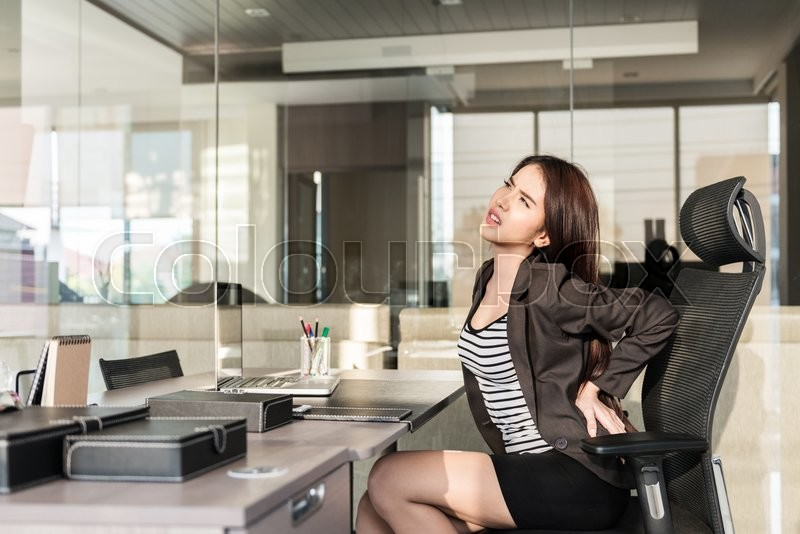 Stock image of 'Young businesswoman having back pain while sitting at office desk'